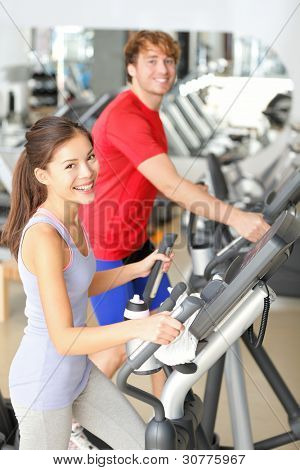 Gym people in fitness center doing walking workout on moonwalker fitness machines. Young couple, asian girl and caucasian man training in gym smiling happy.