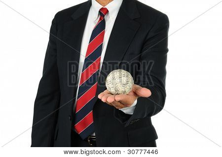 Businessman holding a ball of money in the palm of his hand. Man is unrecognizable, wearing a suit and tie over a white background.