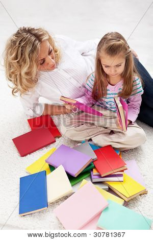 Selecting a story to read - woman and little girl with lots of books
