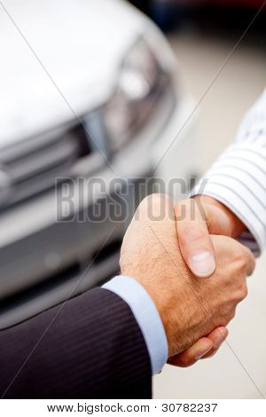 Business handshaking to close the deal after buying a car