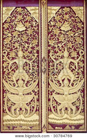 Thai art on wood door with gold work.