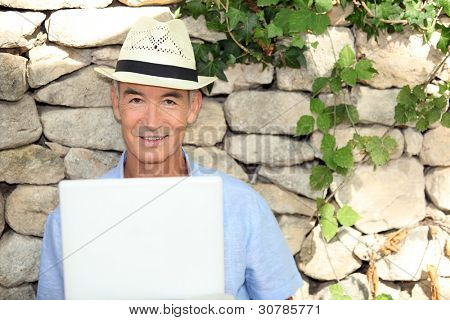 senior man doing computer outside