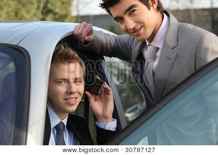 Two businessman by a car.