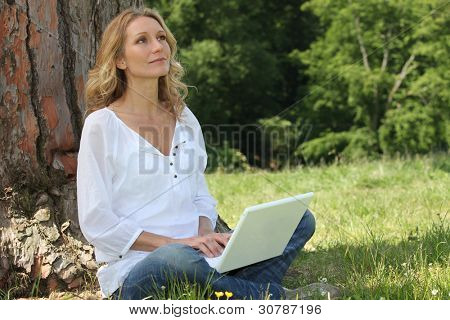 Blond woman sat by tree with laptop deep in thought