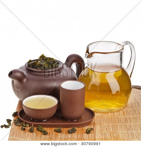 Green tea balls oolong in clay teacup and teacup isolated on white