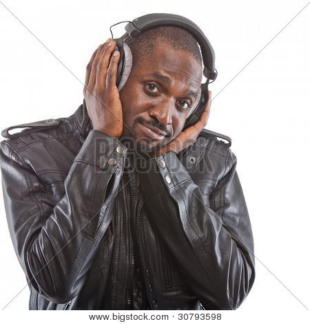Young black man listening to music over his headphones ...