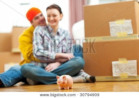 Piggy Bank And Young Family Among Boxes In Background