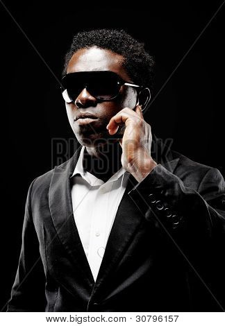 Black african bodyguard or secret agent on a dark background with dramatic lighting gesture towards camera wearing a suit