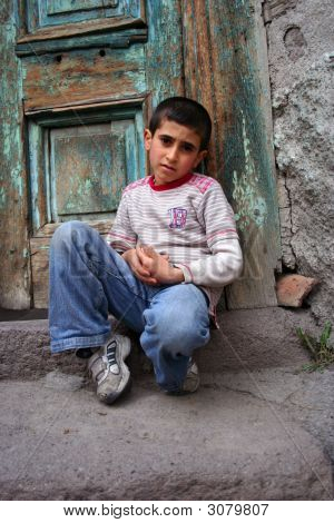 A Boy Sitting At The Doorstep