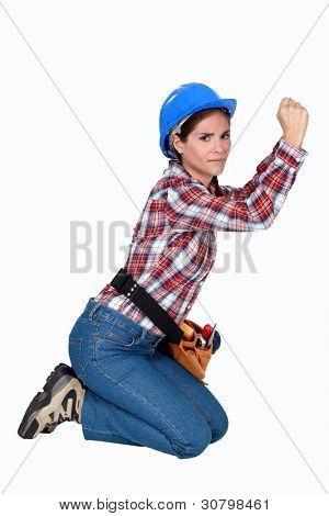 Female building worker kneeling on white background