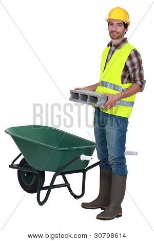 Man placing brick into wheelbarrow