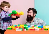 Family Leisure. Father Son Game. Father And Son Create Constructions. Bearded Man And Son Play Toget poster