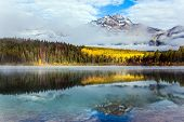 Rocky Mountains, Canada. In the blue water of the Patricia Lake is reflected the snowy peak of the P poster