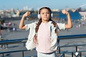 Music Has Healing Power. Adorable Child Enjoy Music Playing In Earphones On Urban Background. Little poster