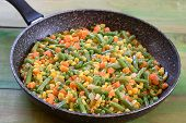 Frying Pan With Roasted Vegetables On Rustic Wood Green Background.green Peas, Carrot, Corn , Green  poster