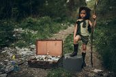 A Homeless Girl Is Standing On A Garbage Dump Next To A Suitcase With Flowers Inside. The Concept Of poster