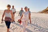 Group Of Senior Friends Walking Along Sandy Beach On Summer Group Vacation poster