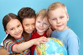 image of school child  - School children holding a globe looking at camera positively - JPG