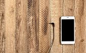 Mobile Phone With Headphones On The Old Wooden Background. Old Mobile Phone Connection To Headphones poster
