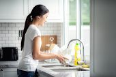 Asian Lady Wash A Dish In Kitchen Room poster