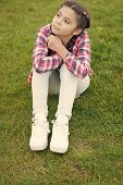 Cute Daydreamer. Girl Little Kid Spend Leisure Outdoors In Park. Girl Sit On Grass In Park. Child En poster