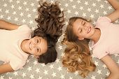 Girls With Long Curly Hair Lay On Bed Top View. Children Perfect Curly Hairstyle Looks Cute. Conditi poster