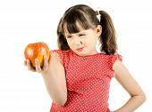 stock photo of disobedient  - disobedient little girl holds apple and makes displeased grimace on white background isolated - JPG
