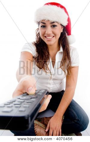 Woman Wearing Christmas Hat And Showing Remote