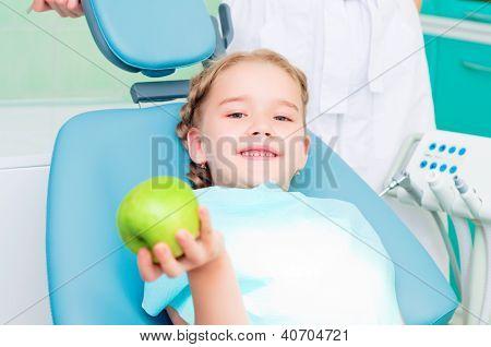 menina na cadeira do dentista mostra uma maçã verde