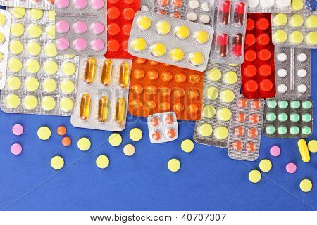 Capsules and pills packed in blisters on blue background