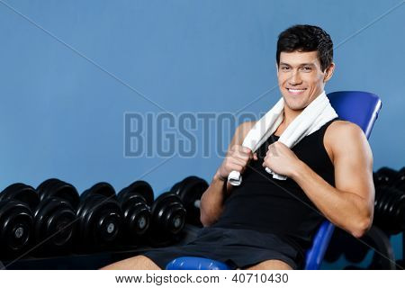 Athletic man rests sitting on blue simulator in gym