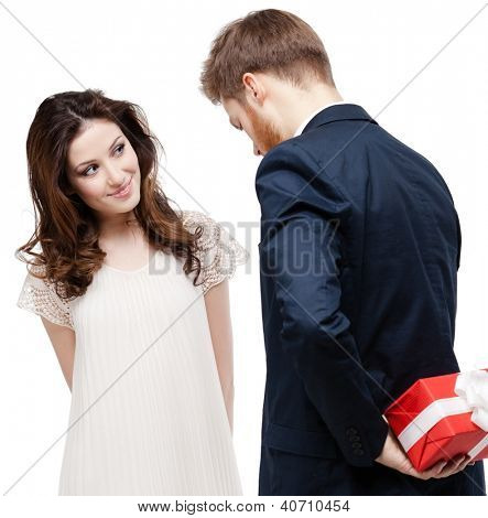 Man hides the present behind the back from his pretty girlfriend, isolated on white