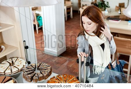 Woman in scarf looking at the bakery glass case full of different pieces of tarts