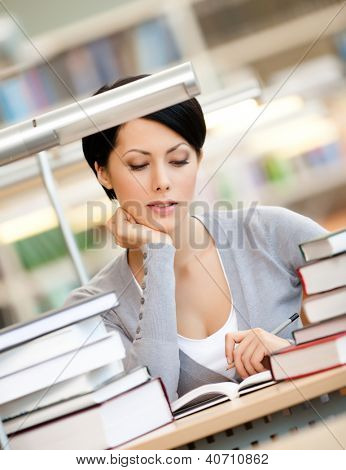 Woman surrounded with piles of books reads sitting at the desk at the library. Educational process
