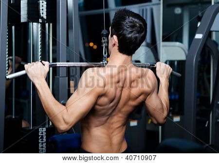 Athletic young man works out on training apparatus in fitness gym
