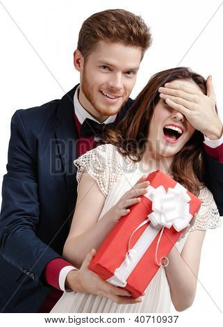Man closes eyes of his girlfriend presenting a gift wrapped in red paper, isolated on white