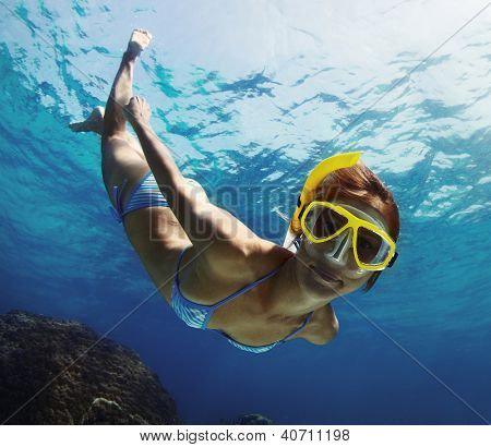 Underwater shoot of a young smiling lady snorkeling and doing skin diving in a tropical sea