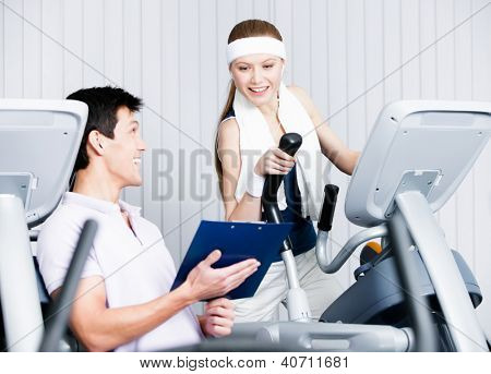 Young woman training on gym training in gym with coach writing down the results