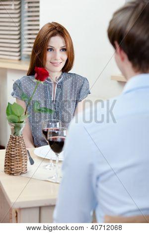 Casal é no restaurante sentado à mesa com o vaso e a rosa escarlate nele