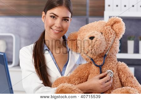 Portrait of young beautiful female doctor examining soft toy with stethoscope.