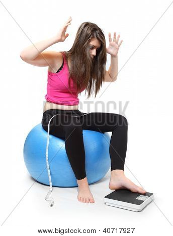 Frustrated woman on a weighing machine.