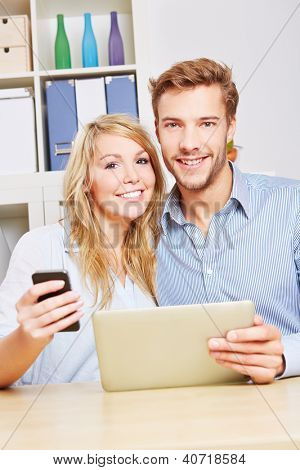 Happy couple with smartphone and tablet computer sitting in the living room