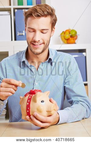 Young attractive man putting Euro money coin in piggy bank