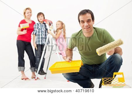 Happy family with kids redecorating their home - painting together