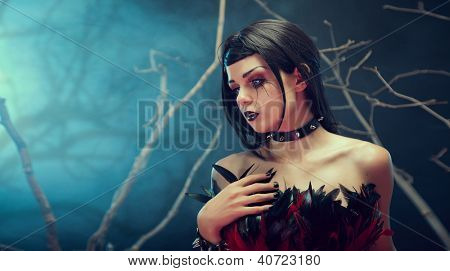 Attractive gothic girl in spiked choker, studio shot with fog and branches