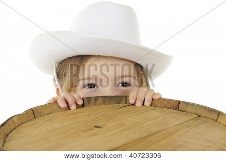Closeup of an adorable preschool cowgirl with only her eyes peering over the top of an old wooden barrel.  Room for your text on the barrel top.  On a white background.