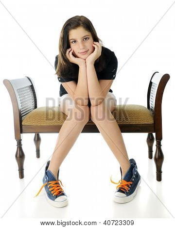 A pretty preteen smiling at the viewer, her head resting on her hands.  She sits on a bench, knock-kneed in over-sized high-tops with neon laces.  On a white background.