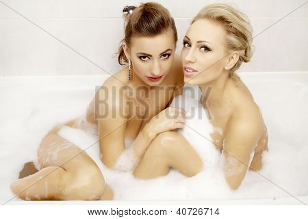 Two attractive brunette and blond woman in bath relaxing. Closeup of young woman in bathtub bathing