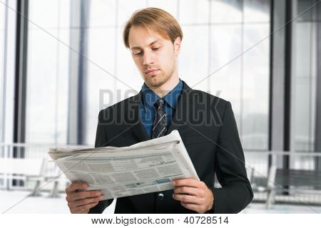 Portrait of a young businessman reading a newspaper