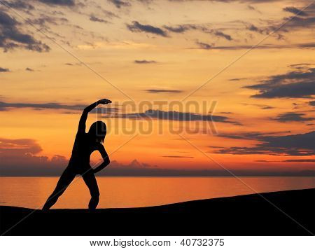 Silhouette of young woman doing exercise over the sunset background